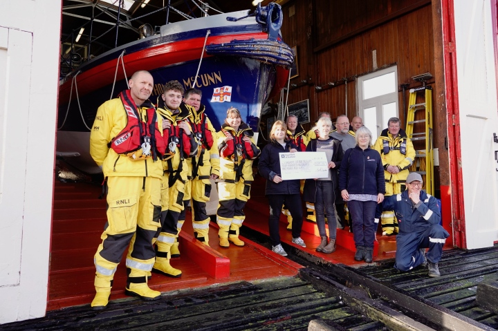 Jewellery designer, Zoe Davidson (left, holding cheque) picutred with members of the RNLI Longhope lifeboat crew and lifeboat museum trustees.jpg
